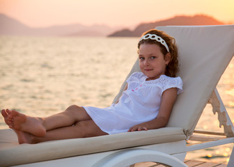 Little beautiful girl similar to mother has a rest on a chaise