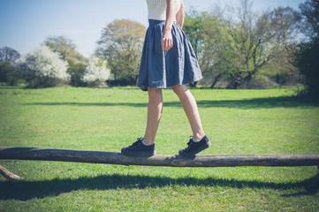 Woman balancing on wooden beam