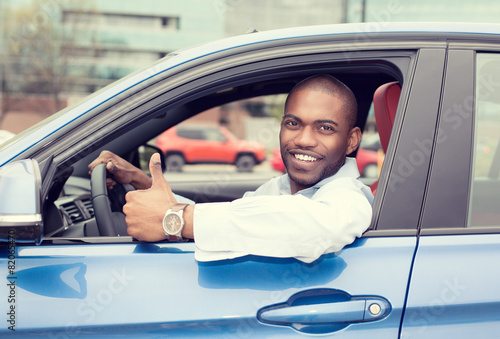 Leinwanddruck Bild Man happy smiling showing thumbs up driving sport blue car