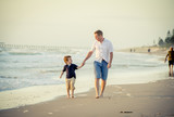 Fototapety young happy father holding hand of little son walking on beach