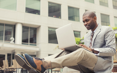 happy businessman working on laptop outdoors