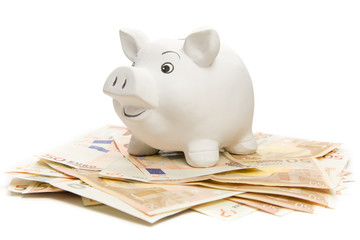 Happy piggy bank on euro banknotes, isolated on white