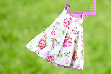 Fashion baby dress hanging on a hanger on a green  background