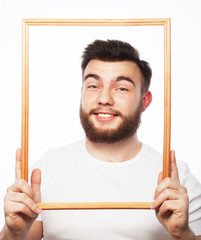 Young man holding picture frame