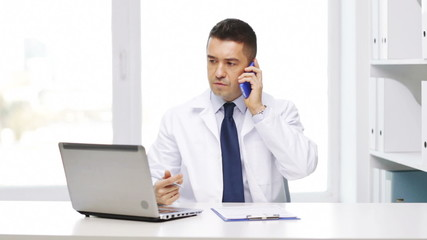 doctor with laptop calling on smartphone