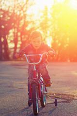 Little boy on a bicycle racing towards his goal against the back