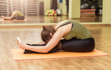 Young woman in a yoga stretching head to knee pose