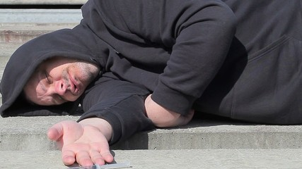 Drug addict man sleeping with syringe near hand