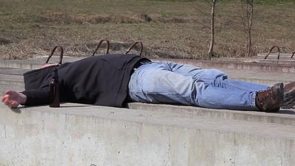 Drunk men sleeping near bottle of alcohol
