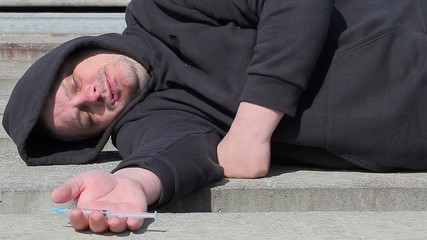 Drug addict man sleeping with syringe in hand at outdoor