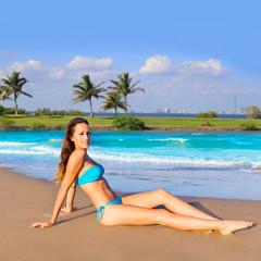 Brunette tourist sitting in beach sand tanning happy