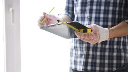 close up of man with measuring ruler and clipboard