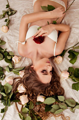 girl who is lying in lingerie on the bed with roses