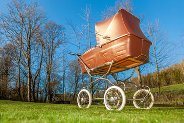 Retro style baby carriage outdoors on sunny day