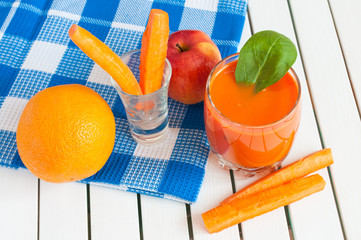 Healthy homemade carrot juice in glass and fresh carrot, apple