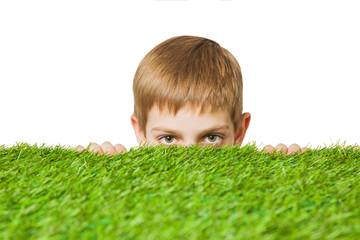 Boy peeping out through grass close up