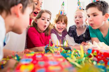 Geburtstagskind pustet Kerzen auf Kuchen aus