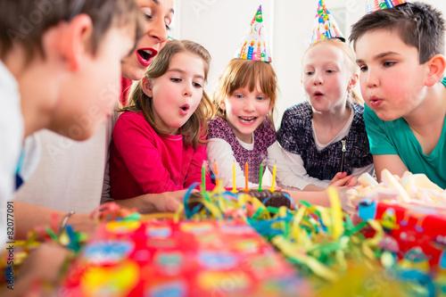 Leinwanddruck Bild Geburtstagskind pustet Kerzen auf Kuchen aus
