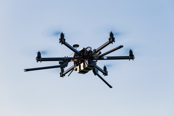 Professional drone hexacopter flying on blue sky