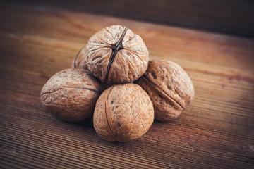 Walnut kernels and whole walnuts wood background
