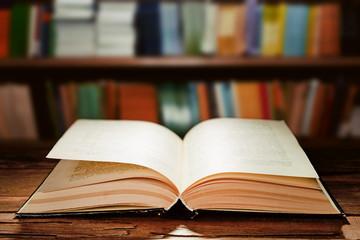 Open book on bookshelves background