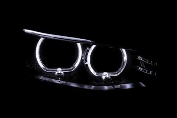 LED headlights of car on black background. Exterior detail.