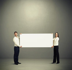 woman and man holding white banner