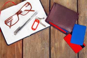 Open notebook, pen, key, glasses and wallet