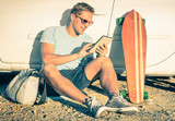 Young hipster man with tablet sitting during car trip travel