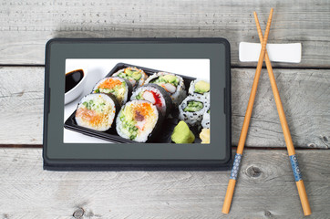 Online Japanese food delivery concept with sushi rolls on an ele