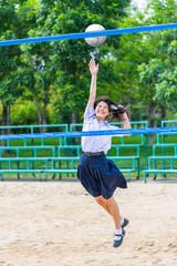 Cute Thai schoolgirl is playing beach volleyball in school unifo