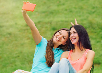 two women friends having fun and taking pictures of themselves w