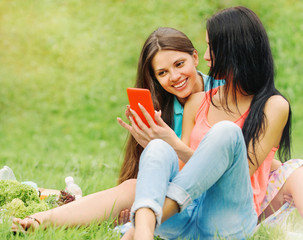 two women friends laughing and sharing pictures in a smart phone