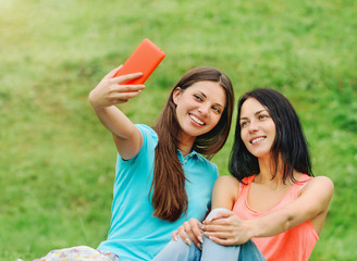 two women friends smiling and taking pictures of themselves with
