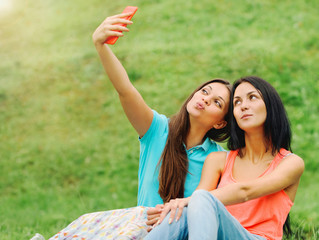 two women friends taking pictures of themselves with phone on pi