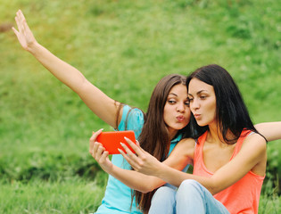 two women friends taking pictures of themselves with smart phone