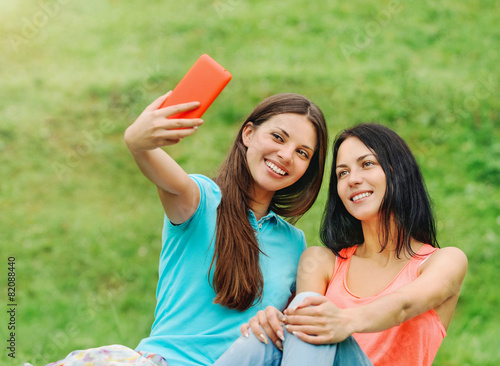 two women friends smiling and taking pictures of themselves with - 82088440