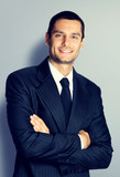 Happy young businessman with crossed arms