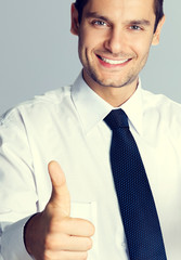 Young smiling businessman with thumbs up gesture