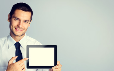 Young businessman showing blank tablet pc