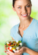 Young happy smiling woman with salad, outdoor