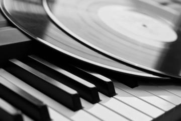 Vinyl record close up lying on piano keys
