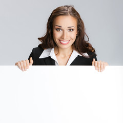 Businesswoman showing signboard with area for text