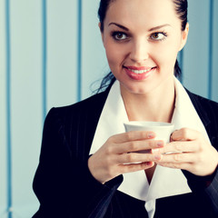 Happy businesswoman with laptop drinking coffee