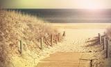 Retro toned photo of a beach path.