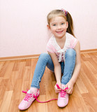 Cute smiling little girl tying her shoes