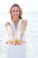 Smiling blonde in white dress holding starfish