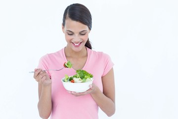Pretty brunette eating bowl of salad