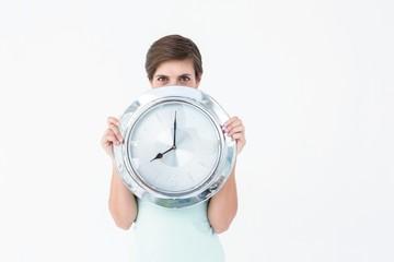 Pretty brunette holding clock