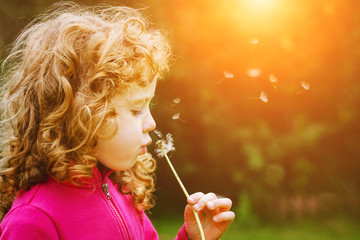Girl blowing dandelion in the rays of the sun.